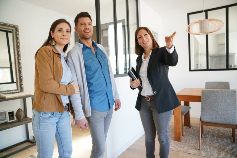 couple looking at model house with real state agent
