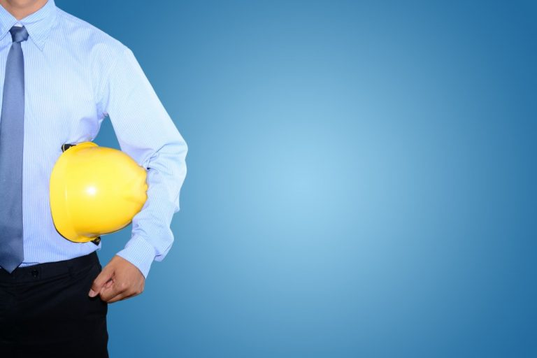 man in corporate attire with safety helmet