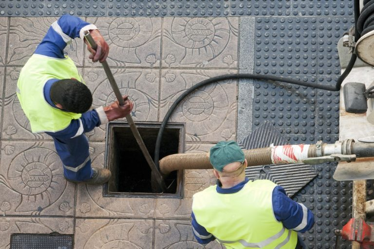 Utilities workers moves the manhole cover to cleaning the sewer line for clogs