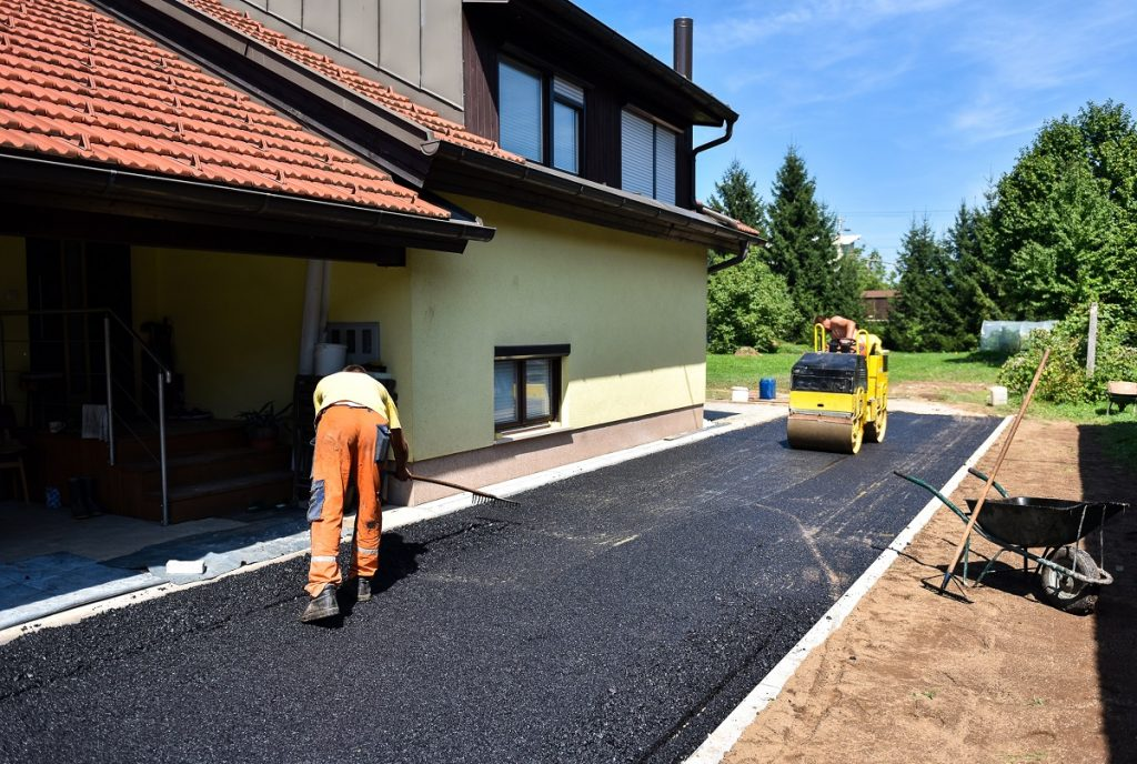 Man making and constructing asphalt road construction with steamroller