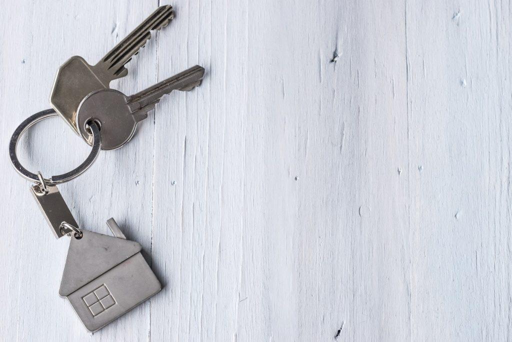 two keys with a house-shaped keychain