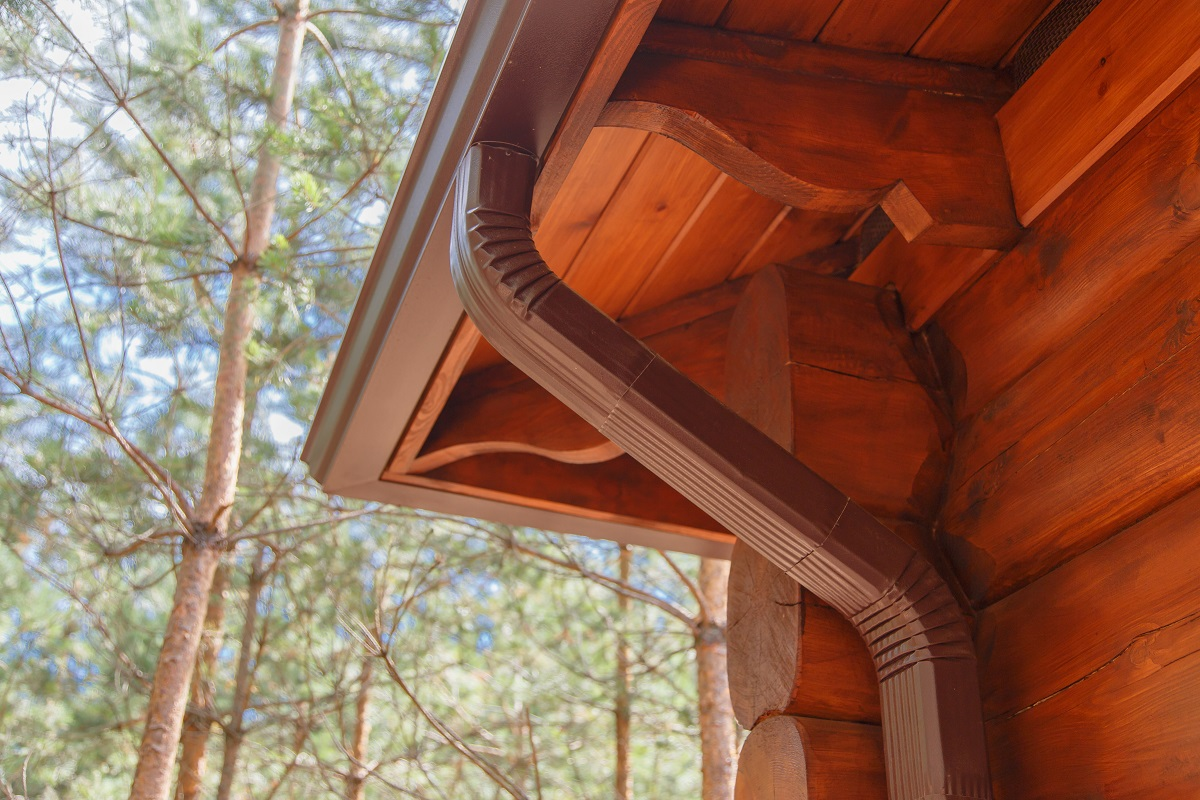 Roof gutter system on log house in forest