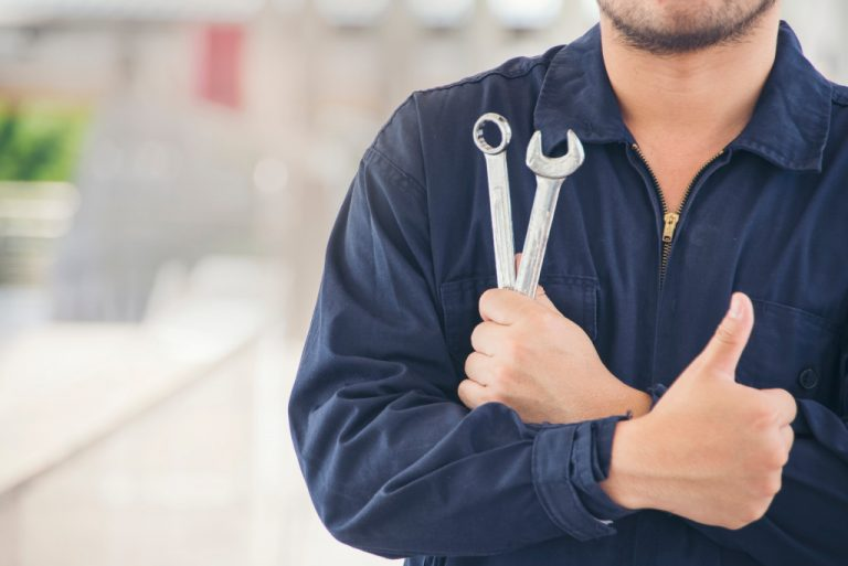 man holding tools and giving thumbs up