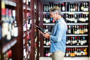 Man looking at wine in store