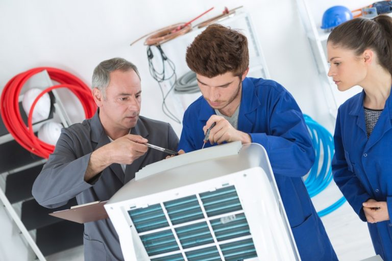 2 men working on air conditioning unit