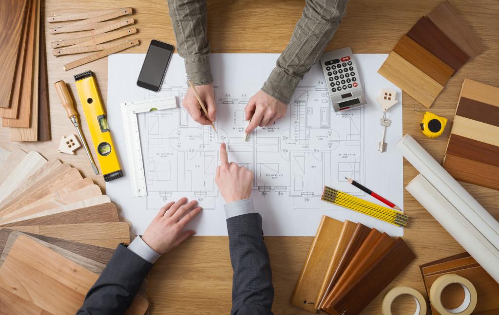 2 pairs of hands on house floorplan