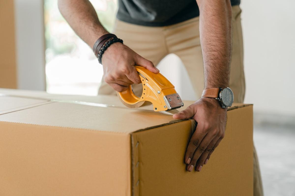 man sealing a package