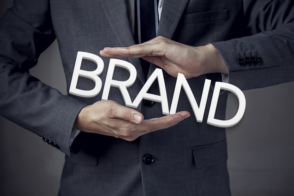 """person in suit holding the word """"brand"""""""