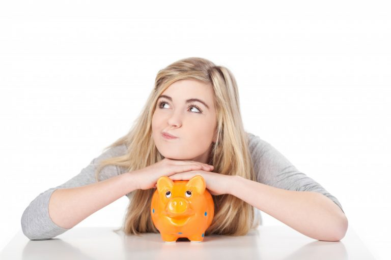 girl resting her head on top of an orange piggy bank